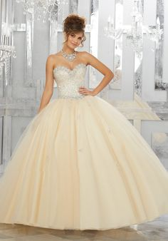 Champagne and Fit for a Fairytale, This Tulle Quinceañera Ball gown Features a Beautifully Beaded Sweetheart Bodice. The Sparkle Tulle Skirt is Delicately Beaded Details Complete the Look. Matching Bolero Jacket Included. Perfect for a Great Gatsby or 1920s theme. Princess Ball Gown Sweet 15 Dress by Vizcaya   Morilee by Madeline Gardner. Style 89143.