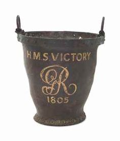 A PAINTED LEATHER FIRE BUCKET FROM H.M.S. VICTORY - DATED '1805' - Of riveted hardened leather with copper band to the top and two iron rings, painted 'H M S VICTORY' with 'GR' cypher and the date '1805', approx. 10 ¾ in. (27.2 cm.) high