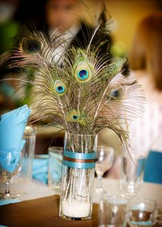 Beautiful peacock feather centerpiece with peacock tail feathers and cylinder vase. #wedding #centerpieces