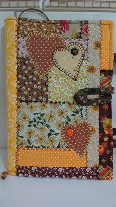 Capa para livro em patchwork confeccionada com tecidos 100% algodão e estruturada com manta R1. Os desenhos e cores podem variar. Possui marcador de página.