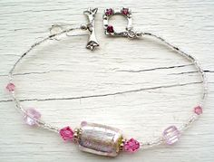 """SOLD. Pink Foil Swirl Bracelet features a Murano foil with pink swirl glass bead, Swarovsky crystals and clasp, Sterling Silver components and seed beads. 7.5"""""""
