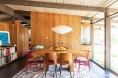 Modern dining area with wooden walls, table, and chairs, accent red chairs, white pendant light, large glass windows, and a bookshelf with leaning art.