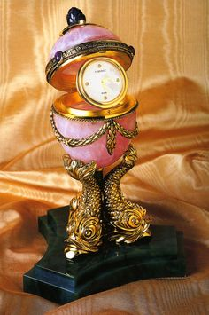"(2) FABERGÉ eggs__ ""Empire Rose Quartz Clock"" Egg ca. 1887.Made of rose quartz and decorated with 24k gilt sterling silver swags, a large amethyst crown, and four agate cabochons. When opened, the egg reveals a Swiss-made clock with mother-of-pearl dial set with four diamonds. The egg is supported by three dolphins cast in 24k gold-plated sterling silver and mounted on a jade base. Limited edition Faberge reproduction. Height 7"""