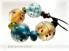 New design from me; small accessory beads in ambers & teals. These are etched matte. Each bead features a transparent color over a core of white with various colored dots, then encased in clear for depth, then trailed with jet black & colored dots for detail. Approx. 17mm diameter. More to come! Renee Wiggins Design 2015