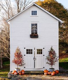 Sweet fall decor in front of a paneled cottage's double Dutch doors.