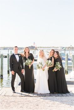bride poses with bridal party on pier at Mantoloking Yacht Club. Dreaming of a classic yacht club wedding? Find inspiration here for your romantic waterfront wedding! Photography by Idalia Photography. #IdaliaPhotography #MantolokingYachtClubWedding #WaterfrontWedding