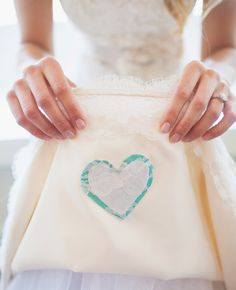 "Still searching for your ""something blue""? Tucked away on the underside of your gown, have your alterations specialist sew a blue heart from a loved one's shirt. We <3 this idea!"