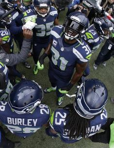 "In this photo made with a fish-eye lens, the Seattle Seahawks ""Legion of Boom"" defensive players including Kam Chancellor (31) and Richard Sherman (25) huddle together outside the tunnel St. Louis Rams before taking the field, Dec. 28, 2014, in Seattle. AP   Read more here: http://www.newsobserver.com/sports/nfl/carolina-panthers/article10214729.html#storylink=cpy"