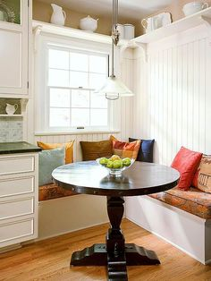 "Space-Smart Banquette. SO PRETTY! ""Banquettes can lend storage space for kitchens with limited cabinet space. The top of this L-shape bench lifts to reveal storage for rarely-used kitchen equipment. An open round tabletop provides plenty of space for casual family dinners and more."""