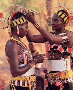 It is customary in traditional African societies for boys and girls to move together to different stages of responsibility and status in the community. These Bassari women from Senegal prepare to participate in the rite of passage marking their entrance to stage five (out of eight.) Their elaborate beaded headdresses with crest-like decorations signify their membership in this level.