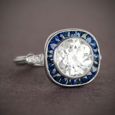 A lively Old European Cut diamond, set within a stunning halo of French cut sapphires, and adorned with diamonds on the shoulder.