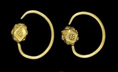 A PAIR OF OSTROGOTHIC GOLD EARRINGS   CIRCA 5TH-6TH CENTURY A.D.   Each with a penannular earwire, round in section, one end affixed to a hollow polygonal bead, the other end tapering, the four main faces of the bead with a cluster of seven granules, the eight smaller faces with clusters of three granules (some lost), with twisted wire around the perforations  1¼ in. (3.2 cm.) wide and 1 3/16 in. (3 cm.) wide