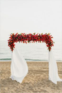 Beach wedding arch with roses. This is the arch every bride would want to marry under. The concast between white and red is undeniably beautiful.