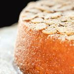 Vertical closeup image of French Almond Cake on a white cake stand