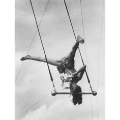 Aerialist Pinito del Oro reads newspaper while balancing on her head on a trapeze bar
