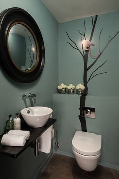 Unleash your creative side. If you're a handy with a paintbrush, decorate a plain bathroom with a simple, striking image, such as this black tree silhouette (complete with quirky pigeon light). If you don't feel confident, simply invest in a beautiful wall decal — just make sure it's suitable for humid conditions.