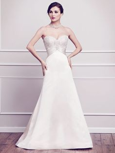 Kenneth Winston Wedding Dresses, Fall 2014. Swarovski encrusted sweetheart bodice with satin wrapped jeweled center piece, finished with a clean satin A-Line silhouette. Zipper back. Fabric: Matte Satin Color Ivory/ Champagne