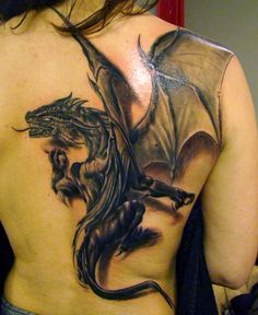 The tattoo artist has given this dragon tattoo design shadows to create a 3D tattoo. The wings are typical of western dragons, resembling the wings of bats.