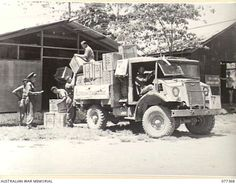 NEW GUINEA. 1944-12-14. PERSONNEL UNLOADING CASES OF AUSTRALIAN COMFORTS FUND GOODS FROM A TRUCK INTO THE UNIT STORE UNDER THE SUPERVISION OF MAJOR HEARN, DIRECTOR.