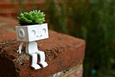 3dprinted Cute Robot Succulent Planter  Sitting Robbie the Robot Planter sitting.  How will you personalize cute Robbie the robot planter by styling his hair with succulents, herbs or cactus?  3d-Printed in sandstone, this cute figurine makes a great gift or a desktop buddy.  Sitting Robbie is one of 3 designs.  Size IN: 2.1 w x 2.5 d x 3.5 h CM: 5.4 w x 6.3 d x 8.9 h  NOTE* the planters do not come with the plant or soil. We arent able to ship organic material.  The shipping and product…