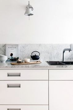 Grey marble splashback and white units in the beautiful home of Swedish interior stylist Pella Hedeby.
