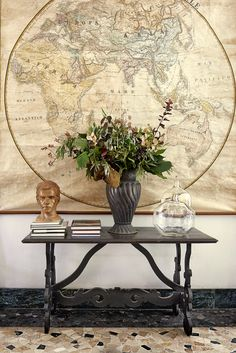 All in soft shades, a detail of the entrance to the house, like a nostalgic composition, with its old map and some beautiful objects, including a bust of the 1930s and a vase in brassware.