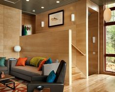 Plywood Walls as Natural Tastes : Amazing Contemporary Living Room With Exciting Plywood Walls Also Dark Gray Modern Couch And Black Modern Armchair Also Blue And Orange Cushions Color Also White Comely Table Lamp With Ball Shaped
