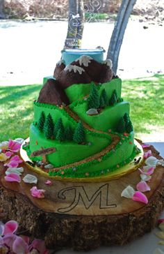 Hiker's Path Wedding Cake - very unique and personalized cake - 4 tiers with a path winding though meadows with flowers and butterflies, up through modeling chocolate trees and snow capped mountains - on a monogrammed rustic wood slab base - Top Tier Wedding Cakes in southern Oregon