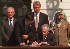 Foreign Minister Peres signs the Mideast peace agreement on Sept. 13, 1993. Prime Minister Rabin (left), President Bill Clinton (center) and Palestine Liberation Organization Chairman Yasser Arafat look on from behind. (AP)