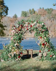 This fall wedding includes a deep red and blue color palette, as well as having details to create a cozy atmosphere. This flower arch was a beautiful centerpiece at the ceremony. Click for inspiration for  your big day! #Wedding #Fall #Colors #Inspiration #Ideas #Cozy #Beautiful | Martha Stewart Weddings -  This Cozy Fall Wedding Took Place on the Riverbanks of Asheville, North Carolina