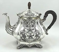 "Simons art nouveau antique sterling silver teapot = A sterling silver art nouveau teapot by the American silversmiths Simons c 1900 with carved wood handle, finial and insulators and four protruding feet. Height 8"" with finial. Width across 9""; weight 25.8 ozt. Z"