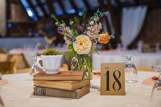 Books, teacup, and flowers...perfection! #tablenumber #centerpiece #weddingdecor #milkglass #kansascity #barnwedding #rustic #vintage #missouri Photo By - Beau Vaughn Photography