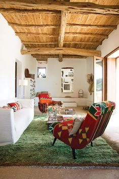 Rug designer Nani Marquina and photographer Albert Font created their home in a peaceful corner of the Spanish party island of #Ibiza. In their living room is a pair of kilim-covered chairs by Philippe Xerri, a chest of drawers by Piet Hein Eek, and a handmade Tunisian #rug provide bursts of color amidst the overall scheme of white, ecru, and cream.