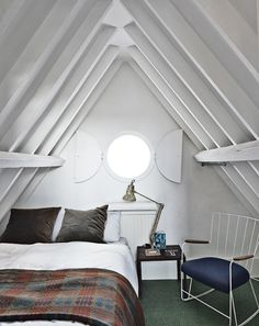 Attic bedroom with plaid wool blanket, modern accent chair and lighting. http://obus.com.au