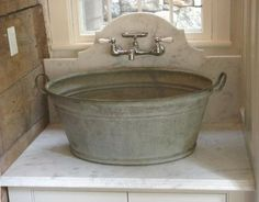 Close-up ~ washtub basin sink with a marble counter and backsplash in a custom laundry room