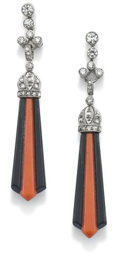 A pair of Art Deco coral and onyx pendants  Each designed as fan-shaped drops composed of a tapered flute of onyx inset with coral, to a rose-cut diamond cap and articulated circular-cut diamond surmount, length 5.2 cm, post fittings.