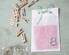 Use mini clothespins to attach inexpensive numbered  wax bags purchased in bulk at Uline to twine stretched a cross a frame.  Choose a soft shabby chic theme to all the bags.  Insert scripture cards, little tokens of love like chapstick, candy and hand-written notes.