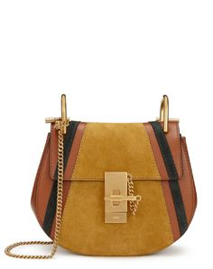 Chloé's iconic Drew bag, loved for its curved silhouette and polished gold hardware, has been refreshed to match this seasons 1970s aesthetic with this soft patchwork leather and suede version. The tobacco leather has been paired with ochre and charcoal suede inserts for a FW16 update. Made in Italy, it is beautifully lined with supple, calfskin suede and has a handy, small slip pocket. The Vogue Edit.