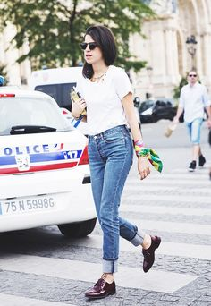 Leandra Medine of Man Repeller wearing a basic white t-shirt tucked into high-waisted cuffed jeans and silk scarf worn as an accessory on the wrist