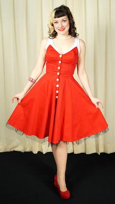 Red Spring Fling Swing Dress:Here's a dress in the color a passion, rubies, and cherries...red! It's a red swing dress with white trim at the bustline, straps and back and has round functional buttons half way down the front. No struggling with a back or side zipper! It has a full swing skirt with a built in black petticoat that hangs at the hem.... $46.00
