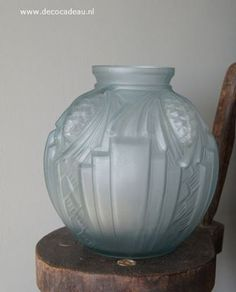 For Sale French* Vase light blue satin-pressed glass, equipped with four stylized pine cones and stepped geometric decorations. The vase signed in relief -P. the Cagny-. For sale.**** Frankrijk* Vaas lichtblauw gesatineerd persglas, uitgevoerd met vier gestileerde dennenappels en geometrische getrapte decoraties. De vaas is gesigneerd in reliëf -P. de Cagny-.Te koop.