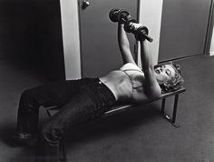 Marilyn working out with barbels wearing a bikini top and jeans. Photographed by Philippe Halsman
