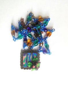 Blue, green abstract polymer clay necklace with glass beads.