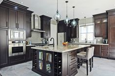 Custom Kitchen, dark countertops, built in oven, large island with built in wine storage.