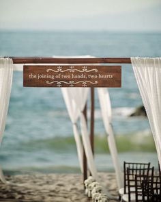 30 Unique Altar Alternatives For Outdoor Weddings: Bypass the standard arch routine and try a unique table setup instead. Use lanterns, flowers, boxes, suitcases — whatever seems to fit in with the rest of your wedding decor.  Source  : Have a special quote or phrase that speaks to you? Hang it from a wooden archway to make it a part of your big day.  Source