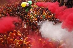 Coloured powders are flung onto revellers during Huranga at the Dauji temple