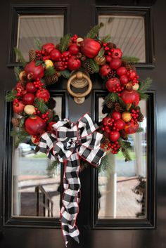 Red apple wreath with check bow. . . looks great against the black door