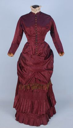 karen-meredith:  SILK BUSTLE DRESS with BEADED TRIM, c. 1880. 2-piece claret satin and taffeta having fringe, buttons and crescent ornament, boned polonaise bodice ruched into back bow, lace collar, underskirt decorated with bands of ruching and pleats, brown cotton lining. Whitaker Auction House.