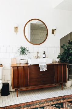 Wood vanity, round mirror and brass accents.
