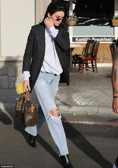 Pricey additions: The reality star completed her look with loose, distressed jeans, black ...
